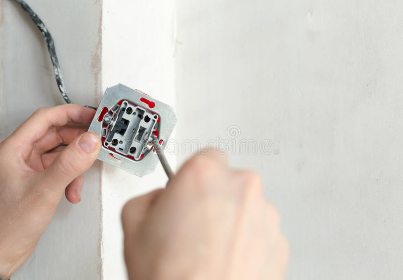 Χέρια ηλεκτρολόγων με το κατσαβίδι που εγκαθιστά την υποδοχή τοίχων στοκ εικόνα με δικαίωμα ελεύθερης χρήσης