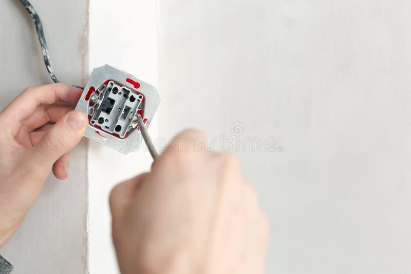 Χέρια ηλεκτρολόγων με το κατσαβίδι που εγκαθιστά την υποδοχή τοίχων στοκ φωτογραφία με δικαίωμα ελεύθερης χρήσης