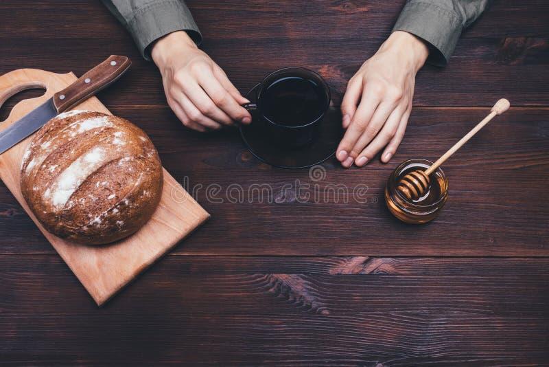 Χέρια θηλυκού που κρατούν το φλυτζάνι του τσαγιού ή του καφέ στοκ εικόνα