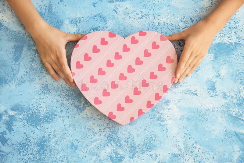 Χέρια καρδιά-διαμορφωμένου κιβωτίου δώρων παιδιών του εκμετάλλευση στο υπόβαθρο χρώματος στοκ φωτογραφίες με δικαίωμα ελεύθερης χρήσης
