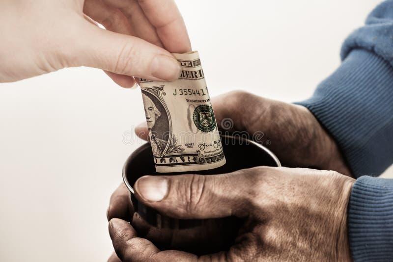Χέρια κινηματογραφήσεων σε πρώτο πλάνο με τα βρώμικα χέρια φλυτζανιών ενός άστεγου ατόμου επαιτών και ενός λογαριασμού δολαρίων τ στοκ εικόνα με δικαίωμα ελεύθερης χρήσης