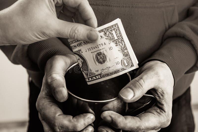Χέρια κινηματογραφήσεων σε πρώτο πλάνο με τα βρώμικα χέρια φλυτζανιών ενός άστεγου ατόμου επαιτών και ενός λογαριασμού δολαρίων τ στοκ φωτογραφία με δικαίωμα ελεύθερης χρήσης
