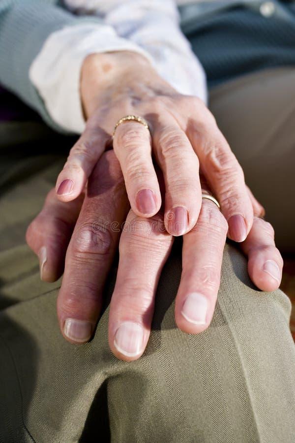 Χέρια κινηματογραφήσεων σε πρώτο πλάνο του ανώτερου ζεύγους που στηρίζονται στο γόνατο στοκ εικόνες με δικαίωμα ελεύθερης χρήσης
