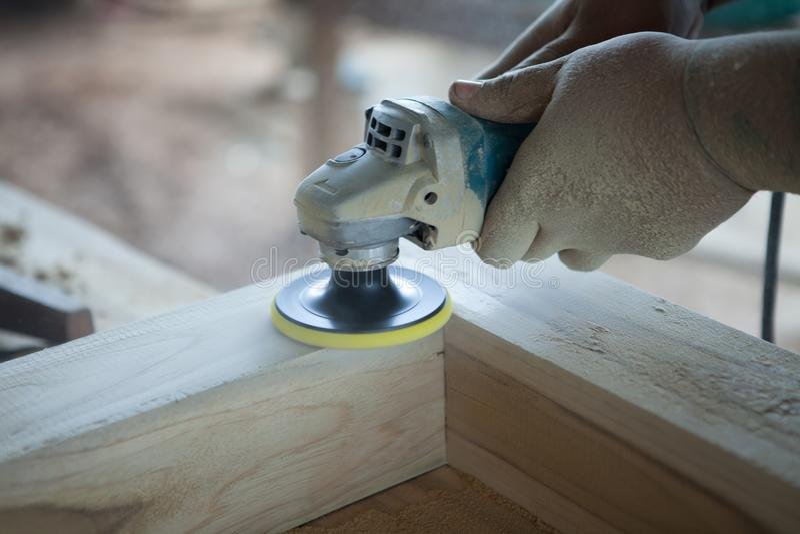 Χέρια κινηματογραφήσεων σε πρώτο πλάνο του ξυλουργού που χρησιμοποιεί ξύλινο sander εργαλείων δύναμης στο wor στοκ φωτογραφία