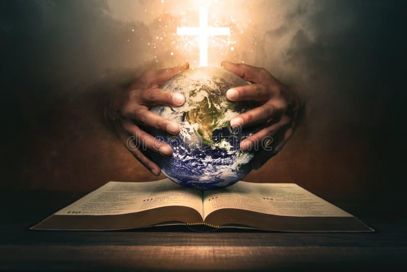 Χέρια κρατώντας τον κόσμο σε μια Αγία Βίβλο στοκ φωτογραφία με δικαίωμα ελεύθερης χρήσης