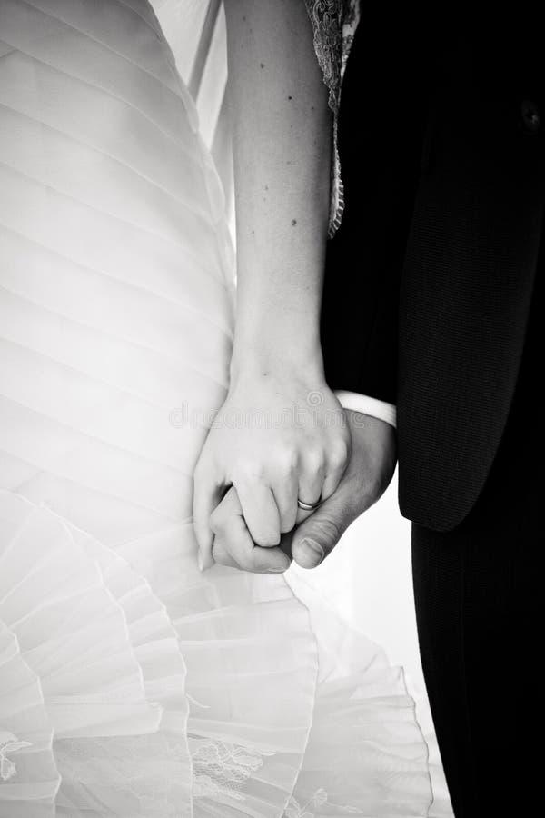 Χέρια λαβής νεόνυμφων και νυφών σε έναν γάμο στοκ φωτογραφία με δικαίωμα ελεύθερης χρήσης