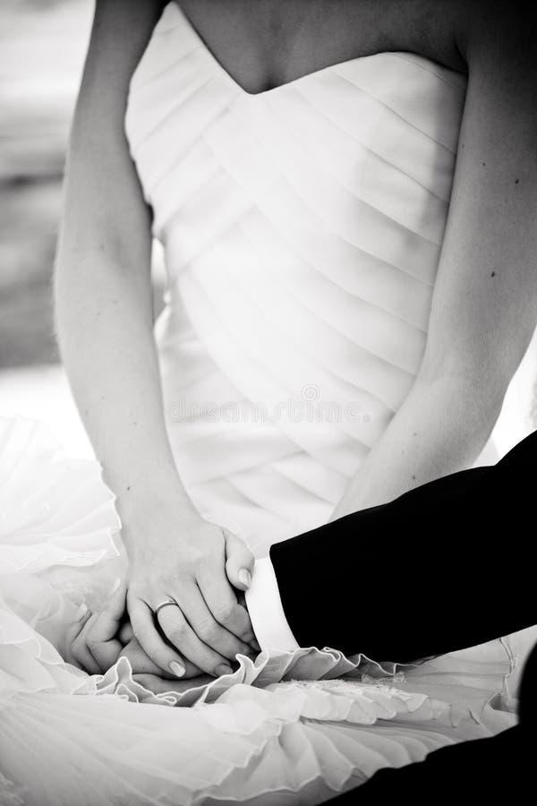 Χέρια λαβής νεόνυμφων και νυφών σε έναν γάμο στοκ εικόνα με δικαίωμα ελεύθερης χρήσης