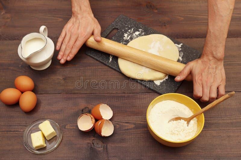 Χέρια μάγειρας που κυλάνε ζύμη για ψήσιμο με καρφίτσα που κυλίζει πάνω στο χαρτόνι σε ξύλινο τραπέζι στοκ φωτογραφία με δικαίωμα ελεύθερης χρήσης