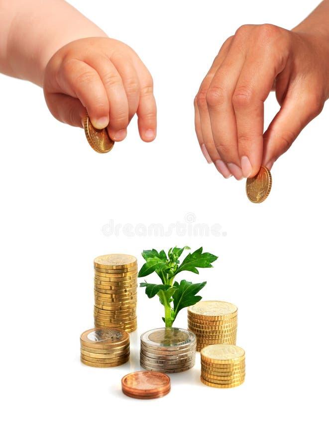 Χέρια με τα νομίσματα και τις εγκαταστάσεις. στοκ εικόνα
