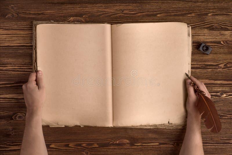Χέρια με τον εκλεκτής ποιότητας στυλό καλαμιών, το μελάνι και το παλαιό βιβλίο στο ξύλινο υπόβαθρο στοκ φωτογραφία