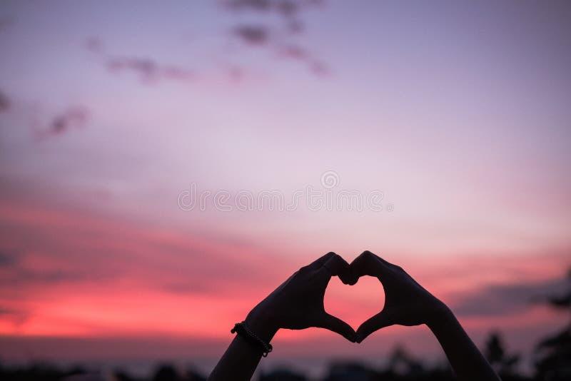 Χέρια με το σημάδι αγάπης στην παραλία στοκ φωτογραφίες