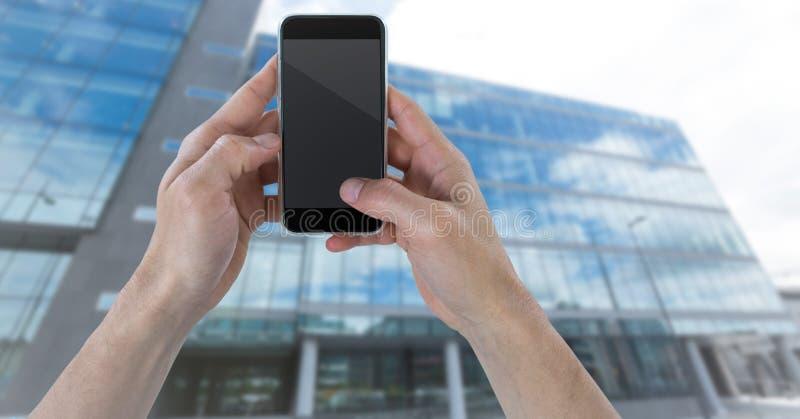 Χέρια με το τηλέφωνο ενάντια στο μουτζουρωμένο κτήριο στοκ φωτογραφία με δικαίωμα ελεύθερης χρήσης