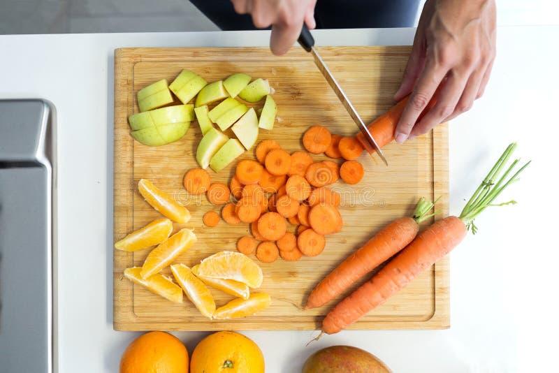 Χέρια μιας γυναίκας που κόβει μερικά λαχανικά και φρούτα στον ξύλινο πίνακα στην κουζίνα στοκ φωτογραφίες