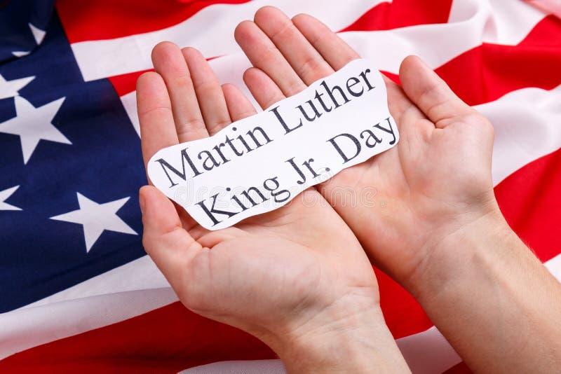 Χέρια μιας εκμετάλλευσης ατόμων στην επιγραφή Martin Luther King Jr παλαμών ημέρα Στα πλαίσια της αμερικανικής σημαίας στοκ φωτογραφία με δικαίωμα ελεύθερης χρήσης
