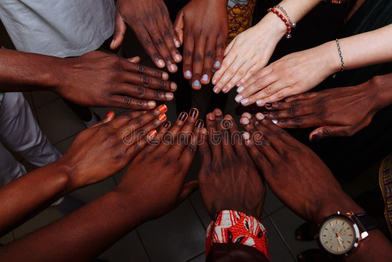 Χέρια μιας ευτυχισμένης ομάδας πολυεθνικών λαών της Αφρικής, της Λατινικής Αμερικής και της Ευρώπης που μένουν μαζί σε κύκλο στοκ εικόνες με δικαίωμα ελεύθερης χρήσης