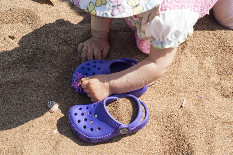 Χέρια μωρών σχετικά με πορφυρό clog με τα ρόδινα λουλούδια στην άμμο στην παραλία Χαριτωμένες λεπτομέρειες των καλοκαιρινών διακο στοκ εικόνα με δικαίωμα ελεύθερης χρήσης