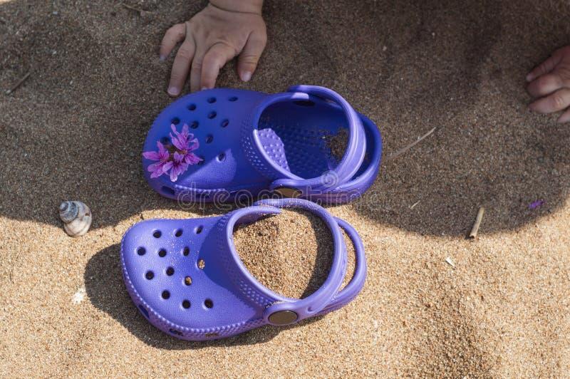 Χέρια μωρών σχετικά με πορφυρό clog με τα ρόδινα λουλούδια στην άμμο στην παραλία Χαριτωμένες λεπτομέρειες των καλοκαιρινών διακο στοκ εικόνα
