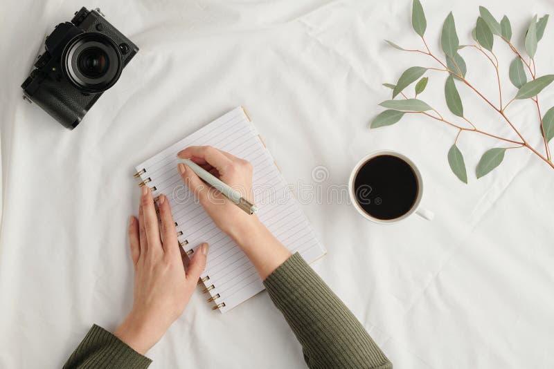 Χέρια νεαρής γυναίκας με στυλό πάνω από ανοιχτό σημειωματάριο που φτιάχνει σημειώσεις εργασίας στοκ φωτογραφίες