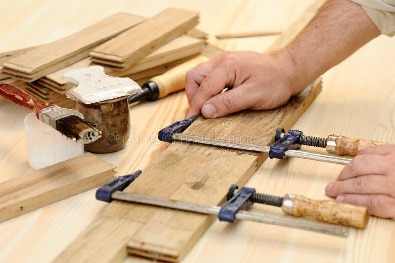 Χέρια ξυλουργών στην εργασία με το σφιγκτήρα στοκ εικόνες