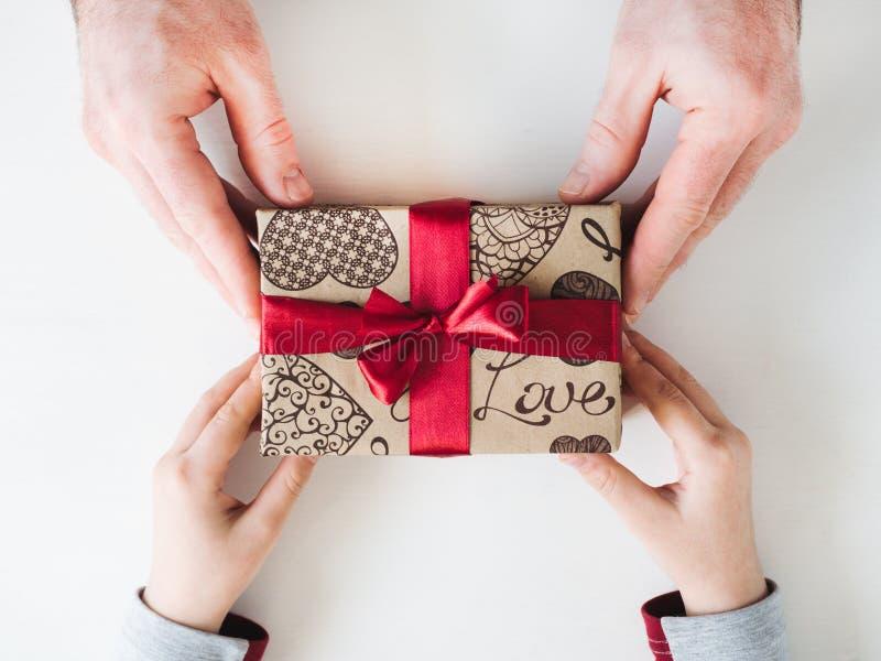 Χέρια παιδιού και ένα όμορφο κιβώτιο δώρων στοκ φωτογραφίες