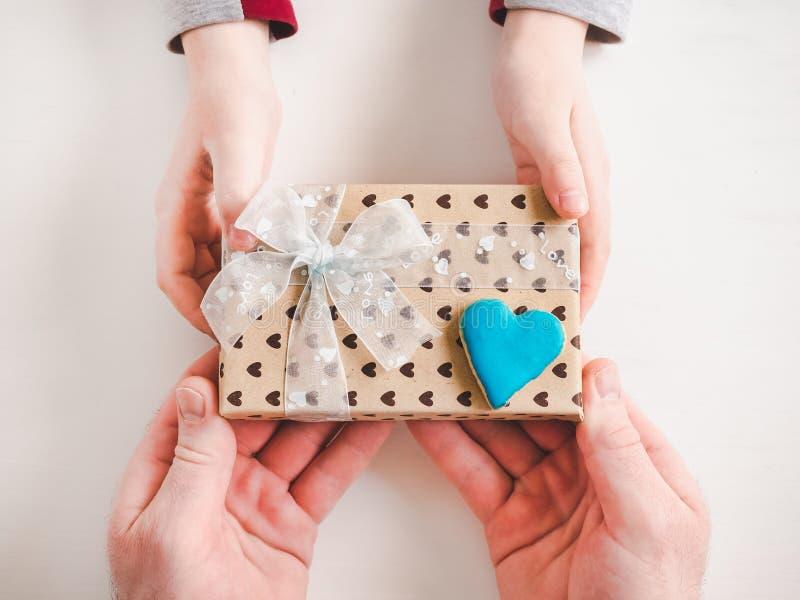 Χέρια παιδιού και ένα όμορφο κιβώτιο δώρων στοκ εικόνα