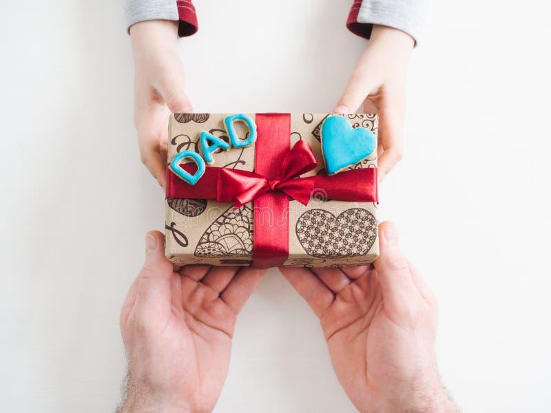 Χέρια παιδιού και ένα όμορφο κιβώτιο δώρων στοκ εικόνες