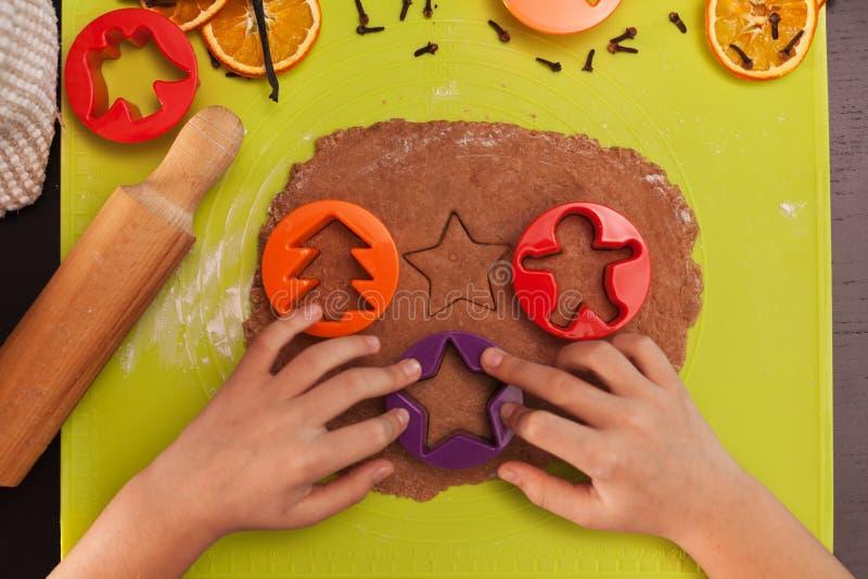 Χέρια παιδιών που κατασκευάζουν τα μπισκότα μελοψωμάτων - τοπ άποψη στοκ φωτογραφία με δικαίωμα ελεύθερης χρήσης