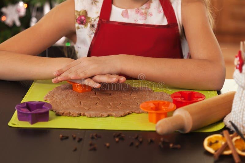 Χέρια παιδιών που κατασκευάζουν τα μπισκότα Χριστουγέννων - ζύμη κοπής στοκ εικόνα
