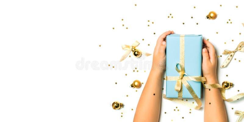 Χέρια παιδιών που κρατούν το όμορφο κιβώτιο δώρων Χριστουγέννων στο άσπρο υπόβαθρο στοκ εικόνα