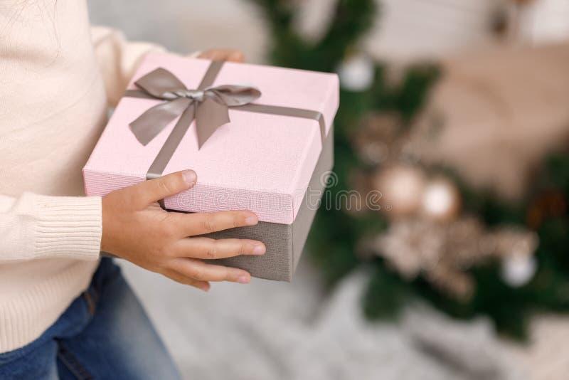 Χέρια παιδιών που κρατούν το όμορφο ρόδινο κιβώτιο δώρων στοκ φωτογραφία