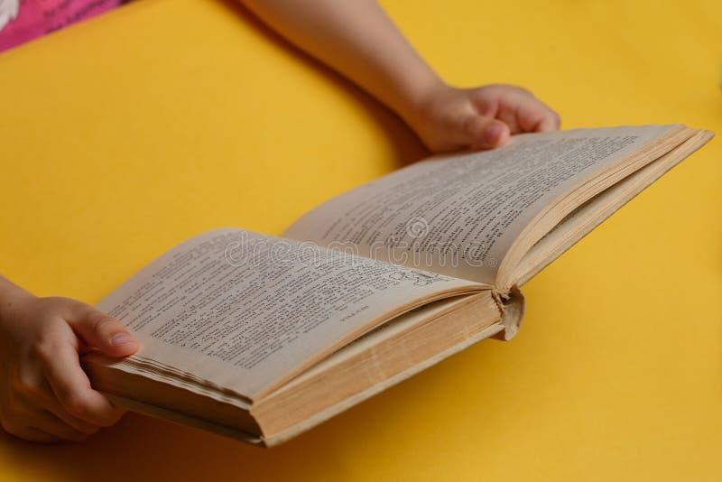 Χέρια παιδιών ` s που κρατούν το βιβλίο στοκ φωτογραφία με δικαίωμα ελεύθερης χρήσης