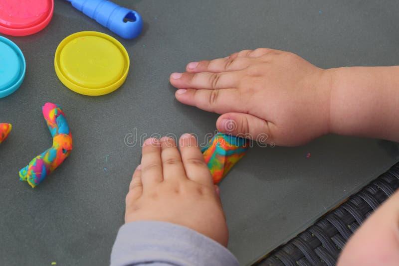 Χέρια παιδιών ` s που παίζουν με το ζωηρόχρωμο plasticine έννοια παιδικής ηλικίας &epsilon στοκ εικόνες με δικαίωμα ελεύθερης χρήσης