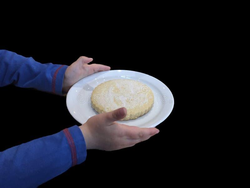 Χέρια παιδιών ` s που κρατούν Biscit στο άσπρο πιάτο με έναν εξυπηρετώντας τρόπο στοκ φωτογραφία