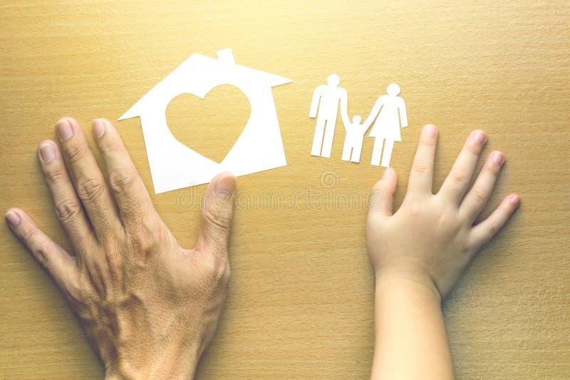 Χέρια πατέρων και κορών με το μικρό πρότυπο του σπιτιού και της οικογένειας στοκ εικόνα με δικαίωμα ελεύθερης χρήσης