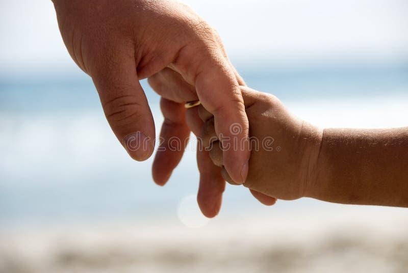 χέρια πατέρων που κρατούν τ&omi στοκ φωτογραφίες