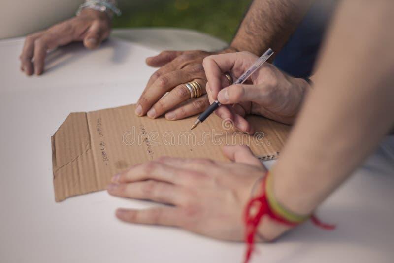 Χέρια που γράφουν σε ένα κομμάτι του χαρτονιού στοκ φωτογραφία με δικαίωμα ελεύθερης χρήσης