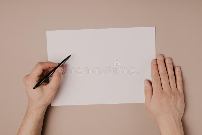 Χέρια που γράφουν στο κενό a4 μέγεθος εγγράφου στο γκρίζο υπόβαθρο στοκ εικόνα με δικαίωμα ελεύθερης χρήσης