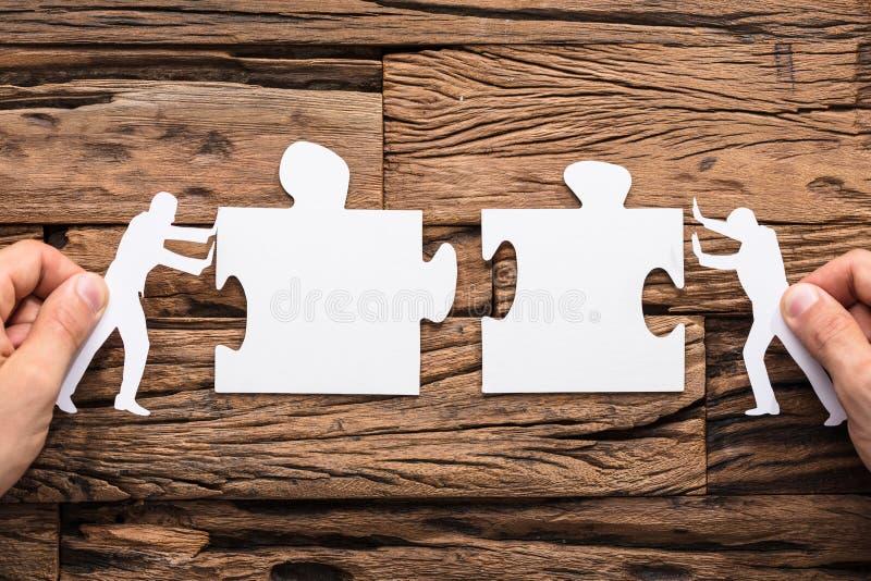 Χέρια που ενώνουν το άσπρο τορνευτικό πριόνι δύο στοκ φωτογραφία με δικαίωμα ελεύθερης χρήσης