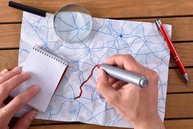 Χέρια που επισημαίνουν μια πορεία σε έναν χάρτη στοκ εικόνες