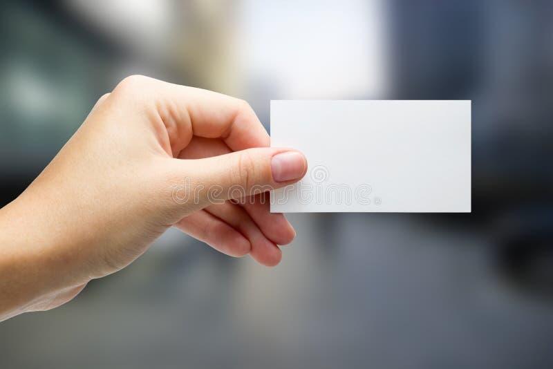 Χέρια που κρατούν μια άσπρη κάρτα επιχειρησιακής επίσκεψης, δώρο, εισιτήριο, πέρασμα, π στοκ εικόνα με δικαίωμα ελεύθερης χρήσης
