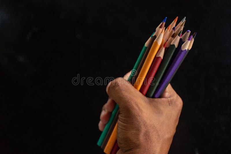 Χέρια που κρατούν μια δέσμη των μολυβιών σε ένα μαύρο υπόβαθρο στοκ φωτογραφία με δικαίωμα ελεύθερης χρήσης