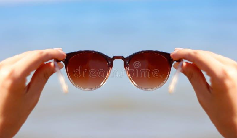 Χέρια που κρατούν τα γυαλιά ηλίου γυναικών ` s στο υπόβαθρο της μπλε θάλασσας και του ήλιου στοκ φωτογραφία με δικαίωμα ελεύθερης χρήσης