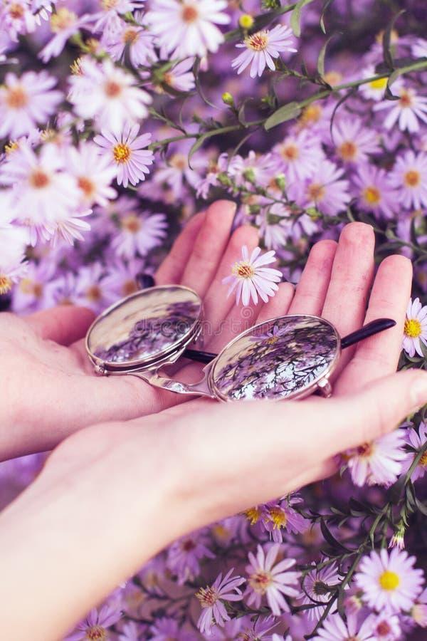 Χέρια που κρατούν τα γυαλιά ηλίου με το υπόβαθρο λουλουδιών στοκ εικόνες
