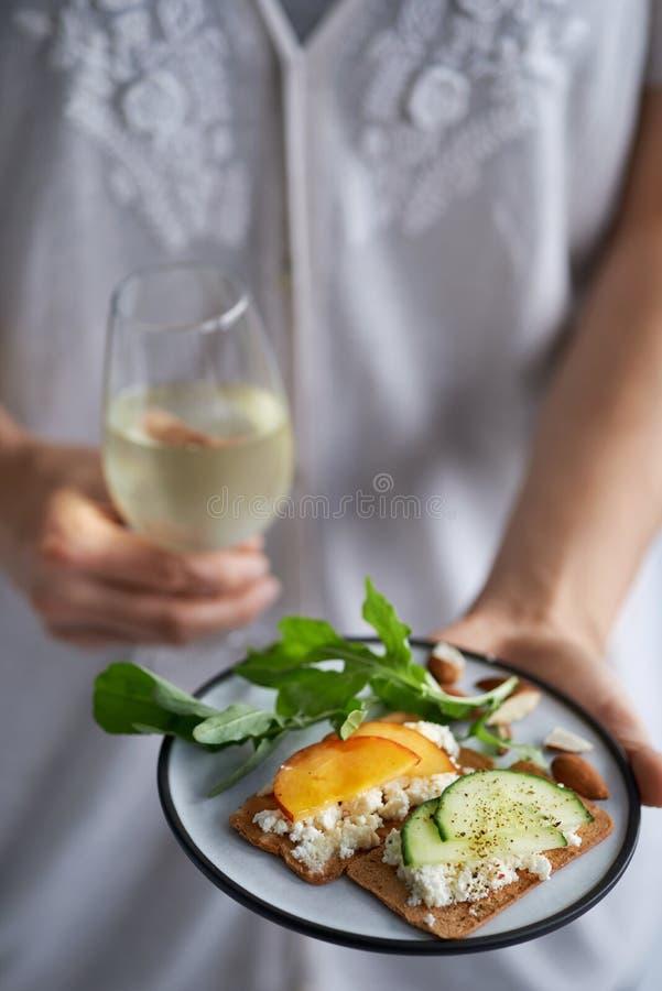Χέρια που κρατούν τα πρόχειρα φαγητά και το κρασί κομμάτων στοκ φωτογραφία