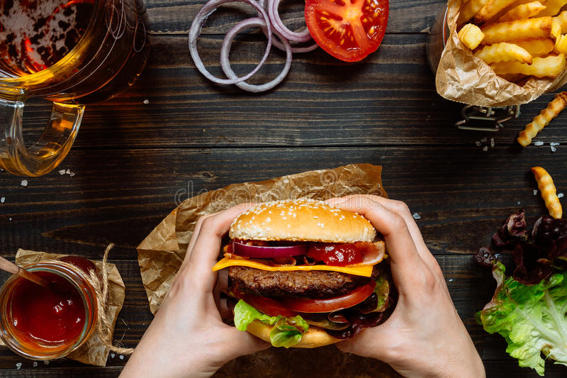 Χέρια που κρατούν τα φρέσκα εύγευστα burgers με τις τηγανιτές πατάτες, τη σάλτσα και την μπύρα στην ξύλινη άποψη επιτραπέζιων κορ στοκ εικόνες