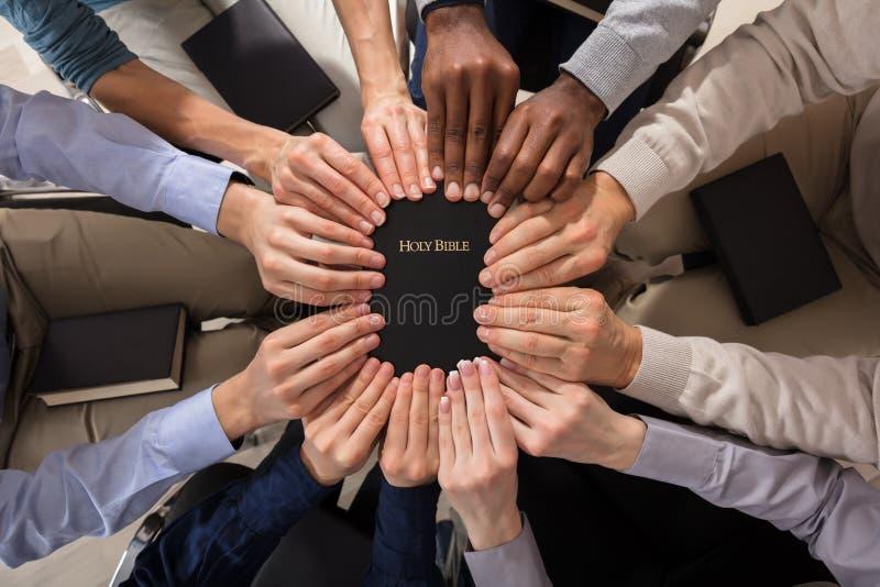 Χέρια που κρατούν την ιερή Βίβλο στοκ φωτογραφία