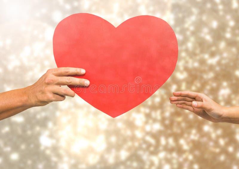 Χέρια που κρατούν την καρδιά με το λαμπιρίζοντας ελαφρύ υπόβαθρο bokeh στοκ εικόνες