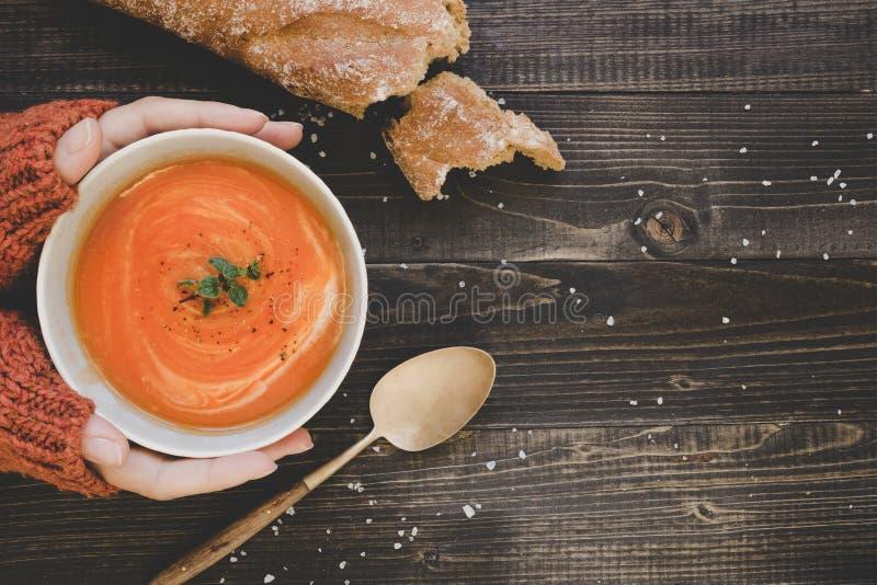 Χέρια που κρατούν την καυτή σούπα κρέμας στον ξύλινο πίνακα, τοπ άποψη Με το διάστημα αντιγράφων στοκ φωτογραφία