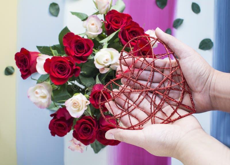 Χέρια που κρατούν την κόκκινη καρδιά μετάλλων με το υπόβαθρο τριαντάφυλλων στοκ φωτογραφίες με δικαίωμα ελεύθερης χρήσης