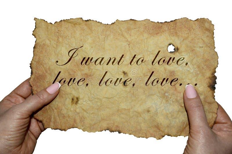 """Χέρια που κρατούν την παλαιά περγαμηνή με τις λέξεις """"θέλω να αγαπήσω, να αγαπήσω, να αγαπήσω ` στοκ φωτογραφία με δικαίωμα ελεύθερης χρήσης"""